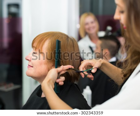 Elderly woman cuts hair at the barbershop
