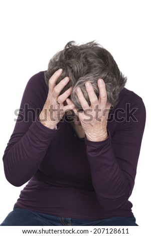 elderly woman depressed and upset holding both hands to her head crying - stock photo