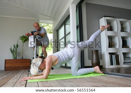 Elderly woman doing fitness next to a man doing bike - stock photo