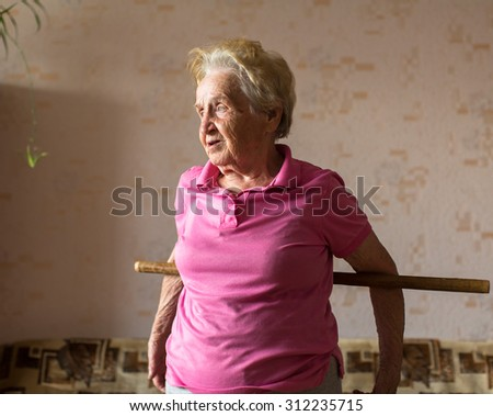 Elderly woman doing rehab exercises with a stick at his home.