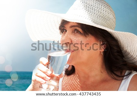 Elderly woman driking water by the sea
