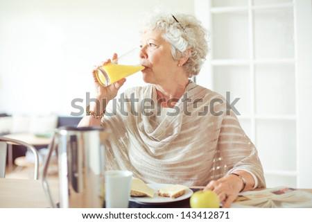 Elderly woman drinking a glass of orange juice - stock photo