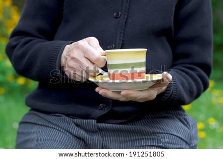 Elderly woman drinking her coffee in the garden - stock photo