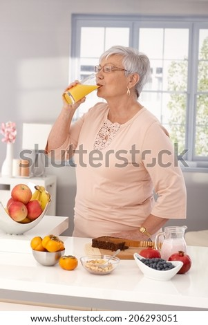 Elderly woman drinking orange juice, preparing healthy breakfast with brown bread and fruits. - stock photo