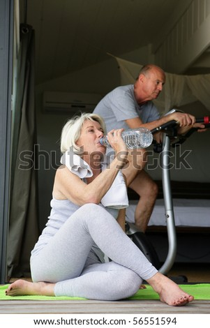 Elderly woman drinking water after exercise near a man doing bike - stock photo