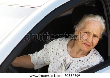 Elderly woman  driving car - stock photo