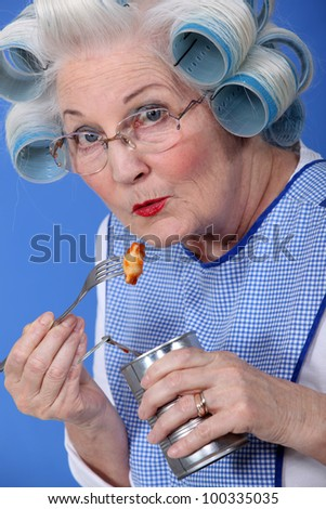 Elderly woman eating from tin can - stock photo