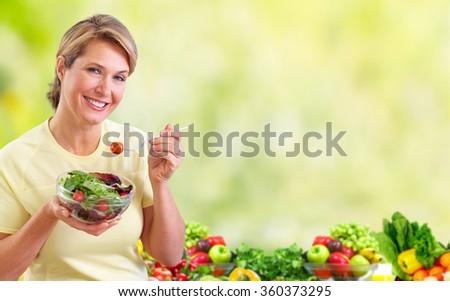 Elderly woman eating salad. - stock photo
