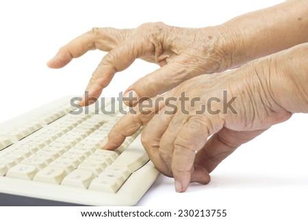 Elderly woman hands on computer keyboard - stock photo