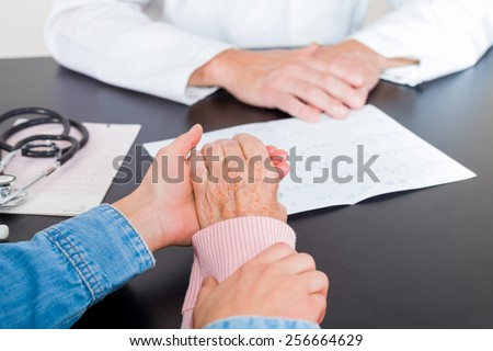 Elderly woman hands supported by carer hands - stock photo
