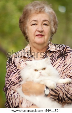 Elderly woman has control over white fluffy Persian cat. - stock photo