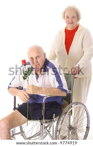 elderly woman helping handicap senior in wheelchair - stock photo