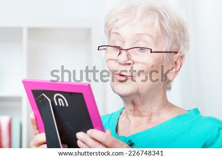 Elderly woman holding frame with family picture - stock photo