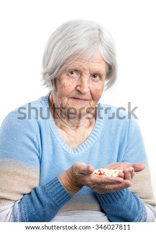 Elderly woman holding handful of prescribed pills over white  - stock photo
