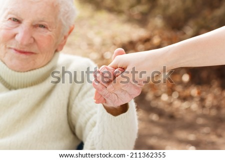 Elderly woman holding hands with young woman outside - stock photo