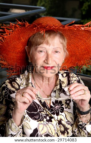 Elderly woman holding her glasses and looking at the camera. Lovely straw hat and rich red lipstick. - stock photo