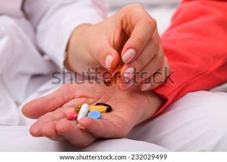Elderly woman holding pills in her wrinkled hand