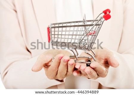 Elderly woman holding small trolley