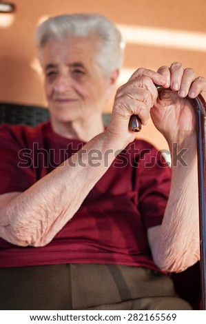 Elderly woman holding walking stick - stock photo