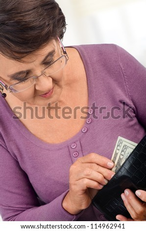 Elderly woman holding wallet with money - stock photo