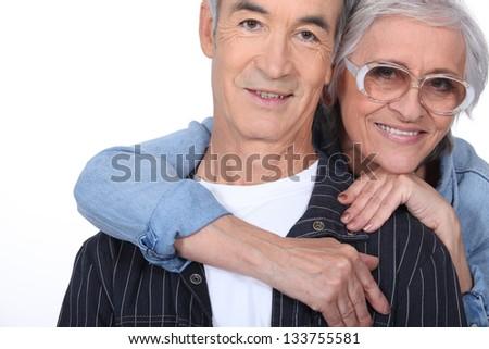 Elderly woman hugging her husband - stock photo