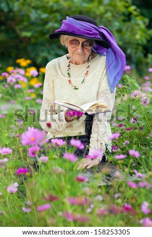 Elderly woman in a beautiful stylish purple hat sitting reading a book on a wooden bench amongst pretty summer flowers in her garden - stock photo