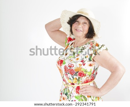 Elderly woman in a summer dress and a hat.  - stock photo