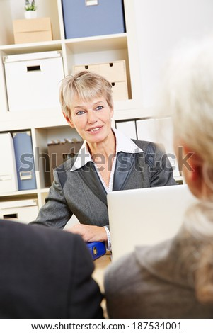 Elderly woman in bank talking to two senior customers about their finances - stock photo