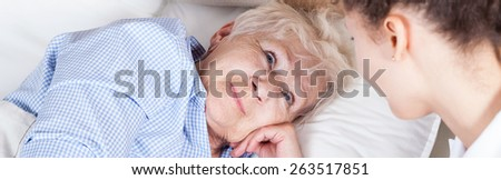 Elderly woman in bed and her nurse - stock photo