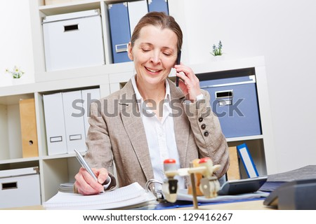 Elderly woman in business office using smartphone to make a call