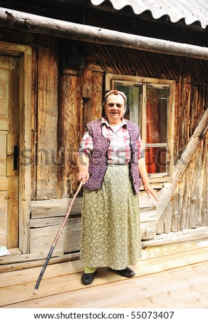 Elderly woman in front of her old house standing with wooden stick in hand - stock photo