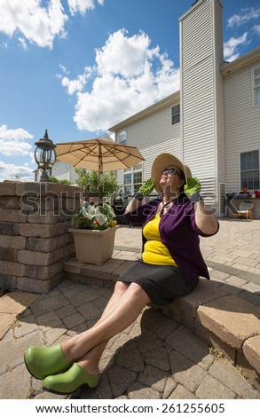 Elderly woman in gardening clothes and a sunhat sitting on the steps of her outdoor patio with her head tilted back enjoying the spring sunshine - spring is here - stock photo