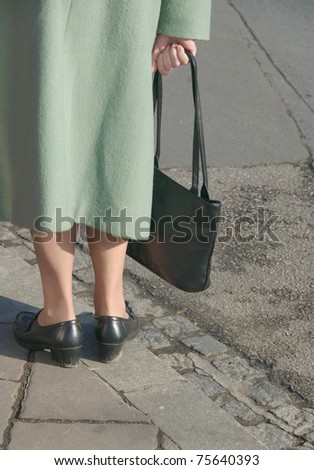 Elderly woman in green coat - stock photo