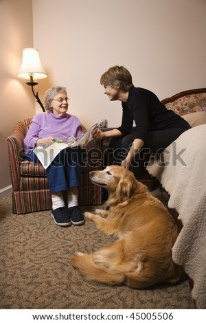 Elderly Woman in her bedroom does needlepoint with a younger woman and a dog in the room. Vertical shot. - stock photo