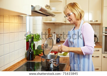 Elderly woman in kitchen on a stove cooking soup - stock photo