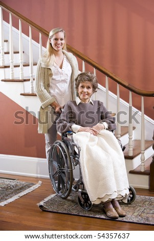 Elderly woman in 70s in wheelchair at home with nurse