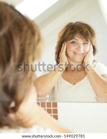 Elderly woman  in the bathroom. - stock photo