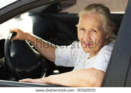 Elderly woman in the car - stock photo