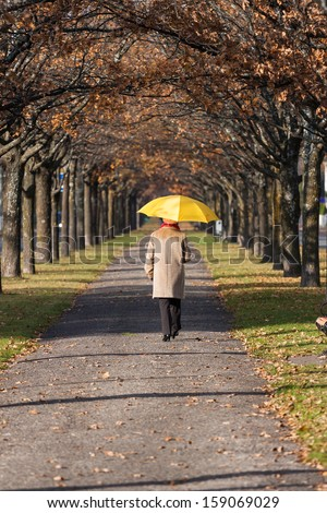 Elderly woman in the fall park with yellow umbrella