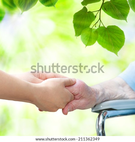 Elderly woman in wheel chair holding hands with young caretaker - stock photo