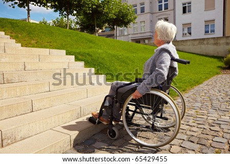 Elderly woman in wheelchair looking at stairs