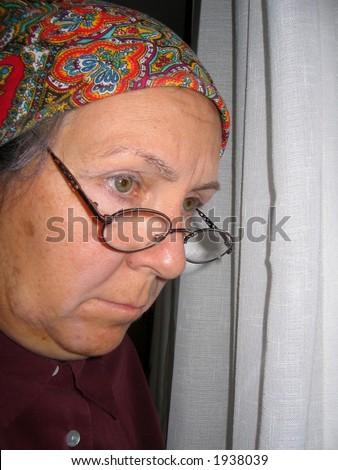 Elderly woman in window - stock photo