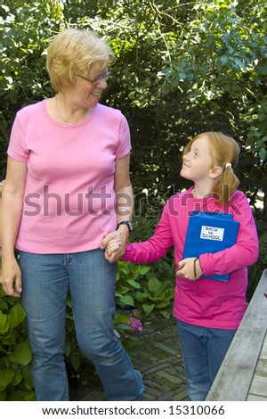 elderly woman is bringing little girl to school - stock photo