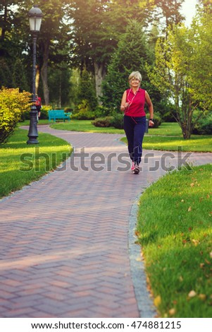 Elderly woman jogging with headphones and smartwatches in the park in evening sunset