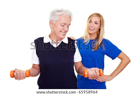 Elderly woman lifting dumbbells with personal trainer - stock photo