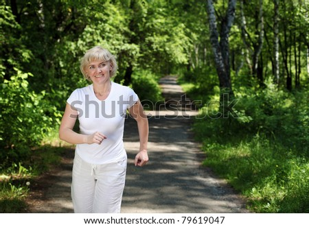 Elderly woman likes to run in the park. Healthy lifestyle - stock photo
