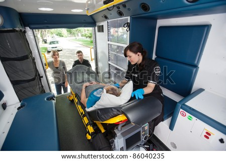 Elderly woman loaded in ambulance being given oxygen - stock photo