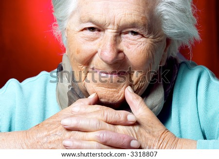 Elderly woman looking at camera, head and shoulders view - stock photo