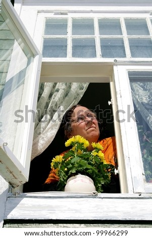Elderly woman looking out of an old fashioned window - stock photo