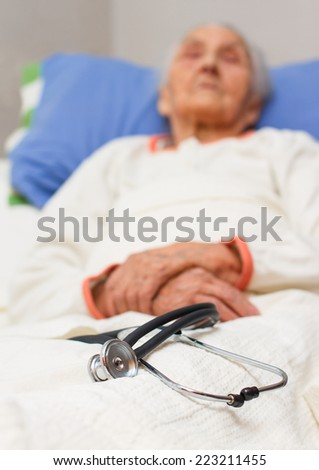 elderly woman lying ill in her bed with a stehoscope , black and white - stock photo